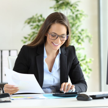 Happy businesswoman wearing suit working using a calculator in a desk at office